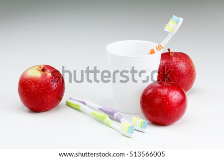 apple with a toothbrush, on white. healthy dental care concepts