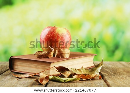 Apple with book and dry leaves on table on bright background - stock photo