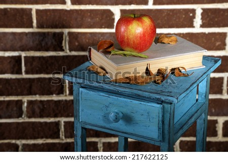 Apple with books and dry leaves on wooden stand on brick background - stock photo