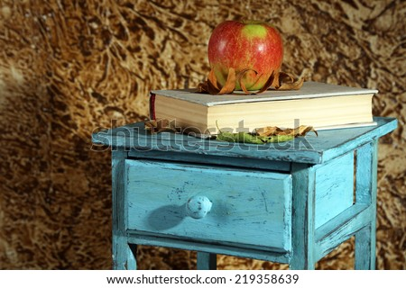 Apple with books and dry leaves on wooden stand on brown background - stock photo
