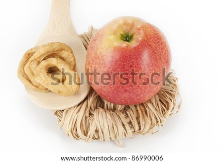 apple with dried apple slices on the wooden spoon - stock photo