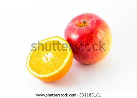 Apple with half orange on white background. - stock photo