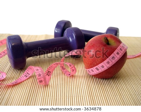 apple with measuring tape and dumbbell - stock photo