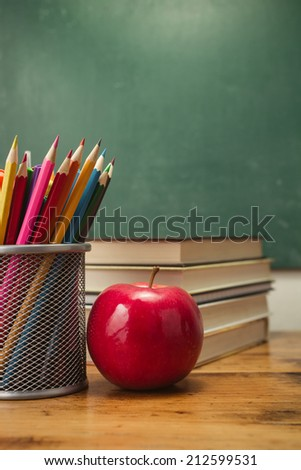 Apple with pencils and stack of books - stock photo