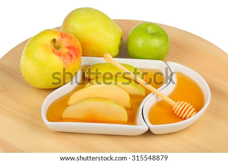 apples and dipping slices of apple in honey for Rosh HaShanah, the Jewish New Year