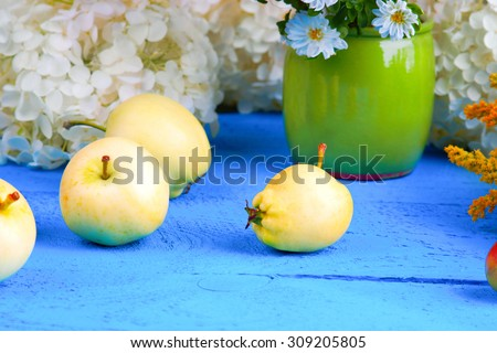 Apples and flowers on a wooden table