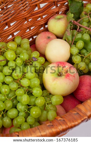 apples and grapes in a basket just harvest