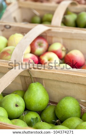 Apples and pears in baskets at farmers market - stock photo