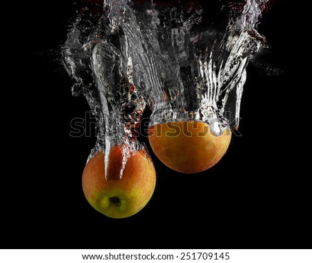 Apples are falling into the water with a splash on a black background. - stock photo