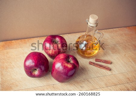 apples, cinnamon sticks and apple cider vinegar on a wooden board