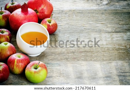 apples, honey and pomegranates on a dark wood background, traditional food for the Jewish new year. Rosh Hashana. selective focus on the middle of the honey - stock photo