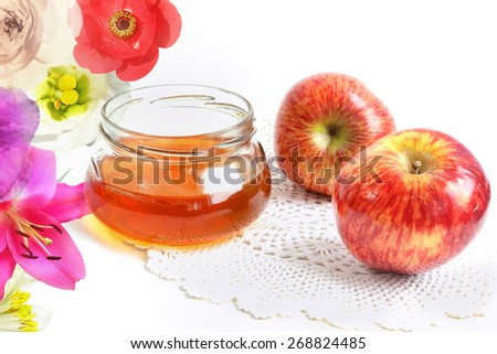 Apples, honey in the glass pot and flowers on a white linen cloth  - stock photo