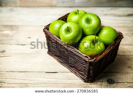 apples in a basket on wooden table - stock photo