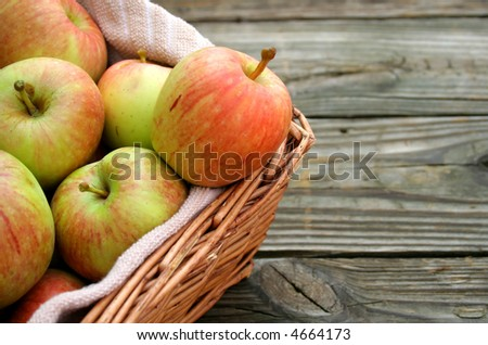 Apples in a basket with wood texture background. - stock photo