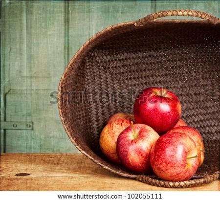 Apples in basket on grunge background, vintage or antique look - stock photo