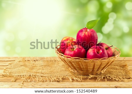 Apples in basket on wooden table over garden bokeh background - stock photo