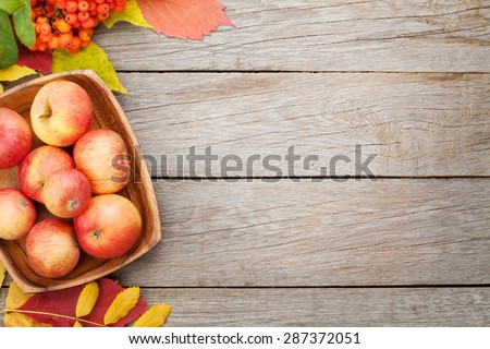 Apples in bowl and colorful autumn leaves on wooden background with copy space - stock photo