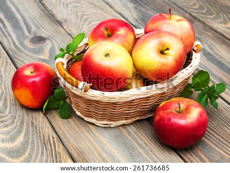 Apples in the basket on a wooden background - stock photo