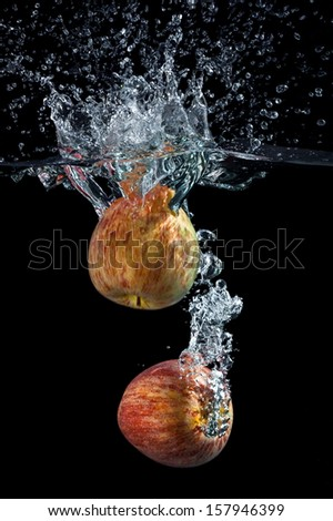 Apples in water on a black background.