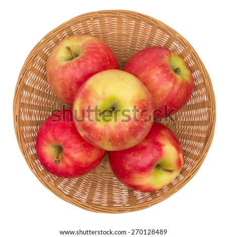 Apples in wicker basket isolated on white, overhead view - stock photo