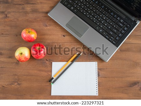 apples, laptop, notebook and pencils  on  old table - stock photo