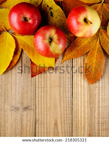 Apples on autumn leaves on wooden background - stock photo