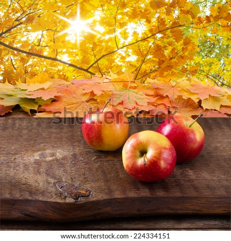 Apples on wooden table over autumn background