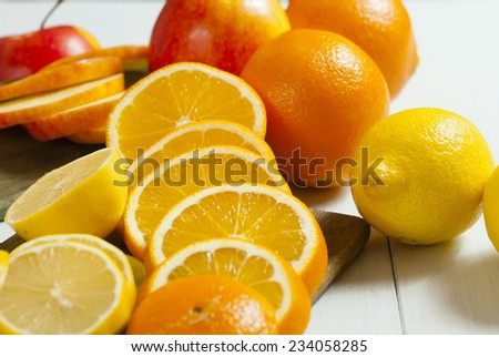 apples, oranges and lemons on white wooden table background