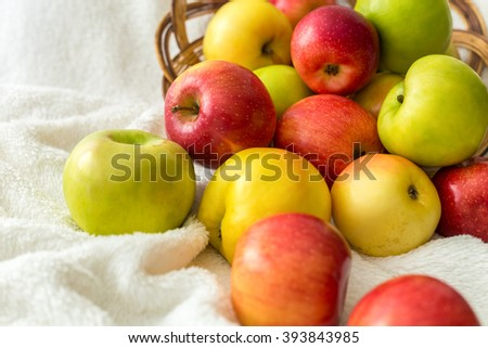 Apples overturned from the basket on white tablecloth
