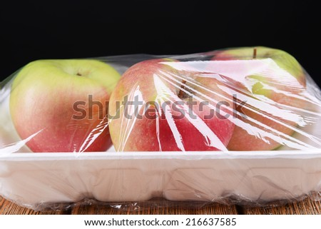 Apples packed in food film on table on black background - stock photo