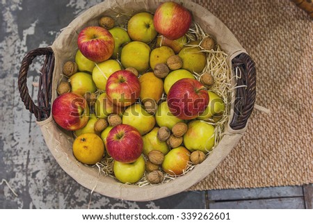 Apples, pears and nuts in a wicker basket. Top view - stock photo