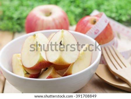 Apples sliced in white bowl on wood table.The concept of food to lose weight. - stock photo