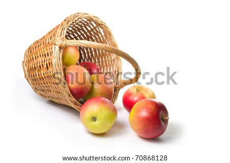 apples spilling out of a basket. - stock photo