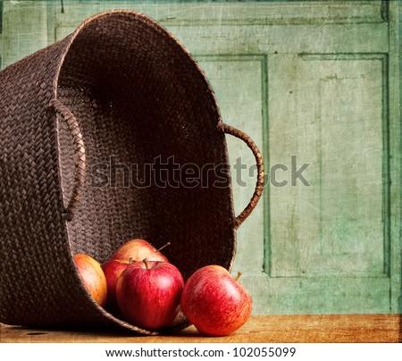 Apples spilling out of a basket on grunge background, vintage or antique look - stock photo