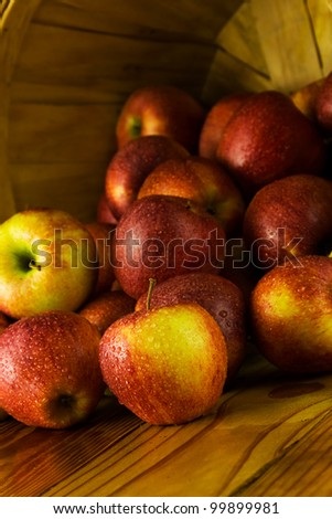 Apples spilling out of a wooden farmer's basket.