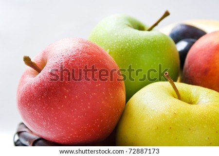 Apples. Various fresh ripe apples in different colors close-up arranged in a wicker basket isolated on neural background - stock photo
