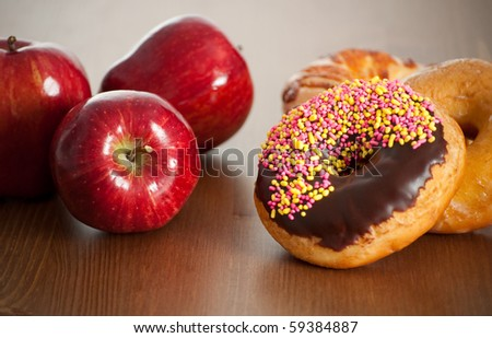 Apples Versus Doughnuts as Snack Option - stock photo