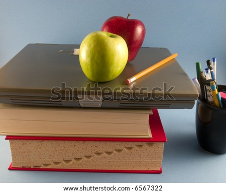 Apples with books, laptop and pens - stock photo
