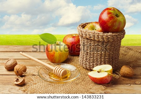 Apples with honey on wooden table over green meadow - stock photo