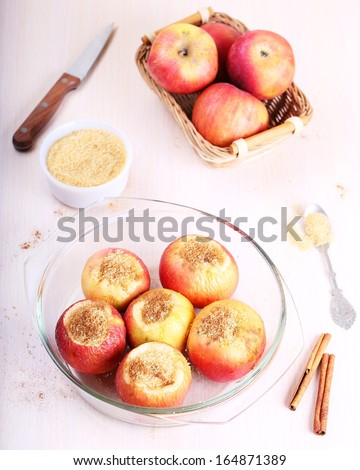 Apples with sugar and cinnamon in a glass baking dish, top view