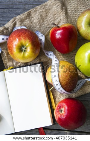 Apples with tape measure, Open notebook for notes. The concept of a healthy lifestyle and losing weight. Free space for text. Copy space. selective soft focus