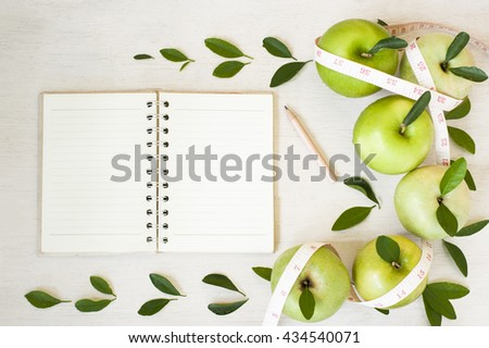 Apples with tape measure, Open notebook for notes. The concept of a healthy lifestyle and losing weight. Free space for text. Copy space. selective focus