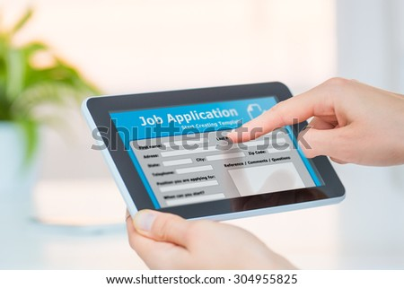 Applicant filling up the online job application by digital tablet. All icons, tablet interfaces where created from scratch by myself. - stock photo