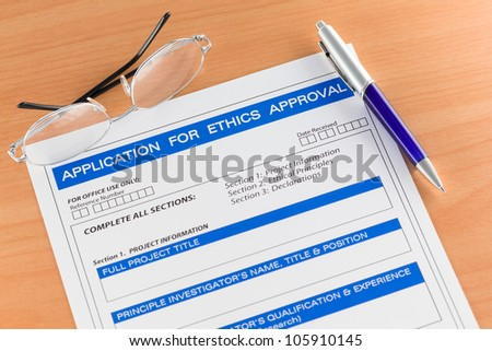 Application for Ethics Approval Form on Table with Pen and Spectacles