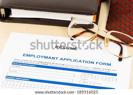 Application form, resume, neck tie, glasses, and planner