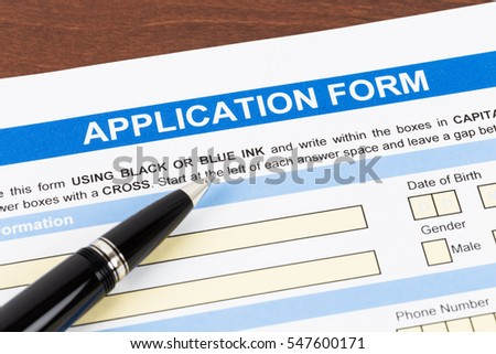 Application form with pen; document is mock-up