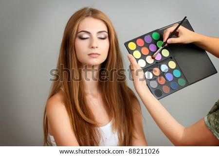application of eyeshadow on a beautiful girl - stock photo