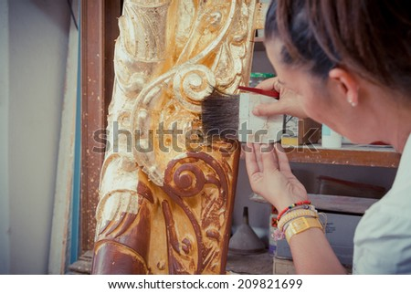 Application of Gold Leaf to an ancient picture frame - stock photo