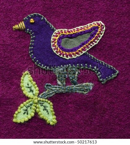 Applique and embroidered bird on a branch with leaves. Demonstrates a variety of techniques. Created by the photographer - stock photo