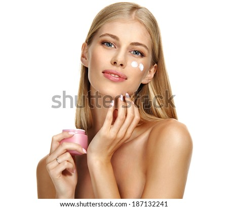 Apply cream on face / studio photography of young girl holds cosmetic cream container - isolated on white background  - stock photo